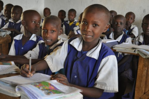 Kenyan school children using books during their lessons
