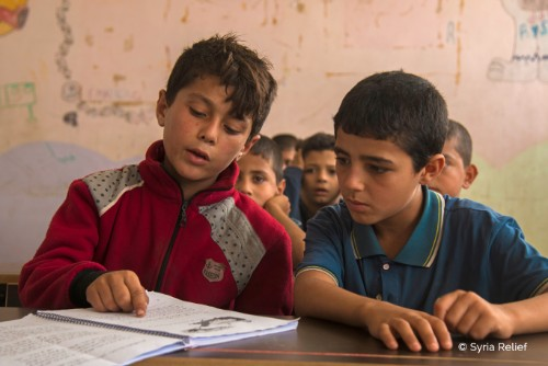 Omar, right, and a friend in their Idlib classroom. Credit Syria Relief